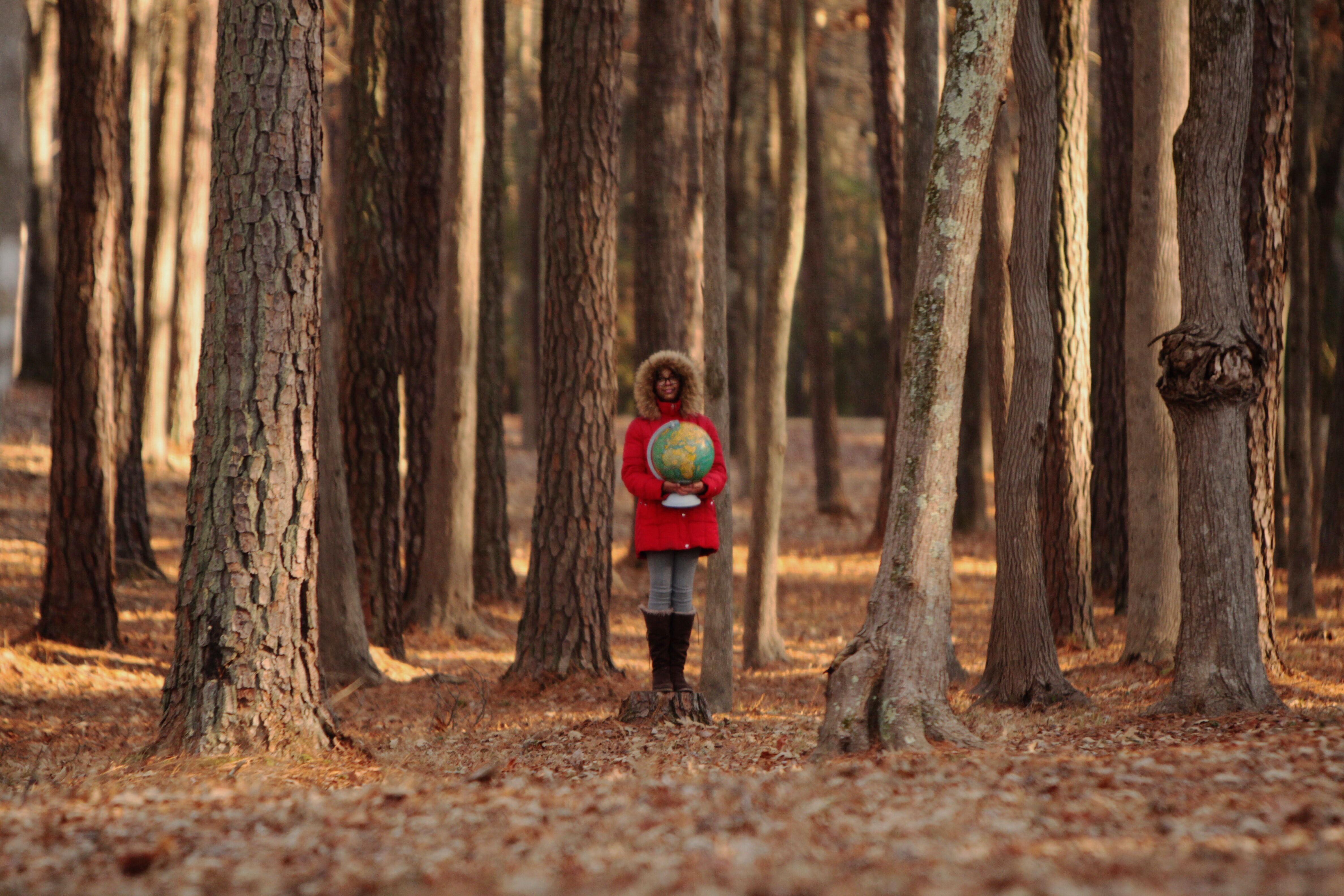 Woman wearing red coat standing in a forest holding a globe