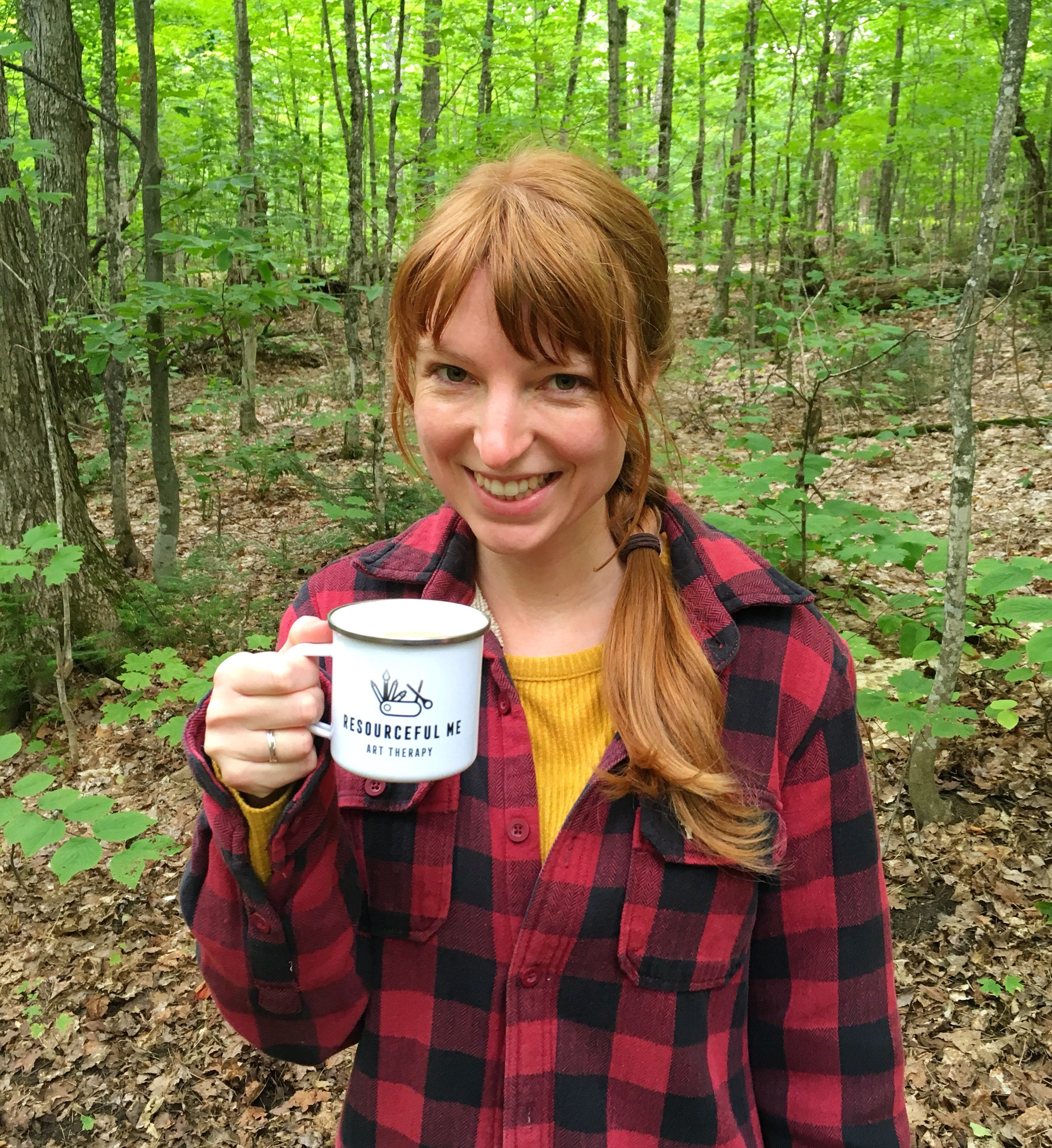 smiling woman standing in front of forest holding tin mug of coffee