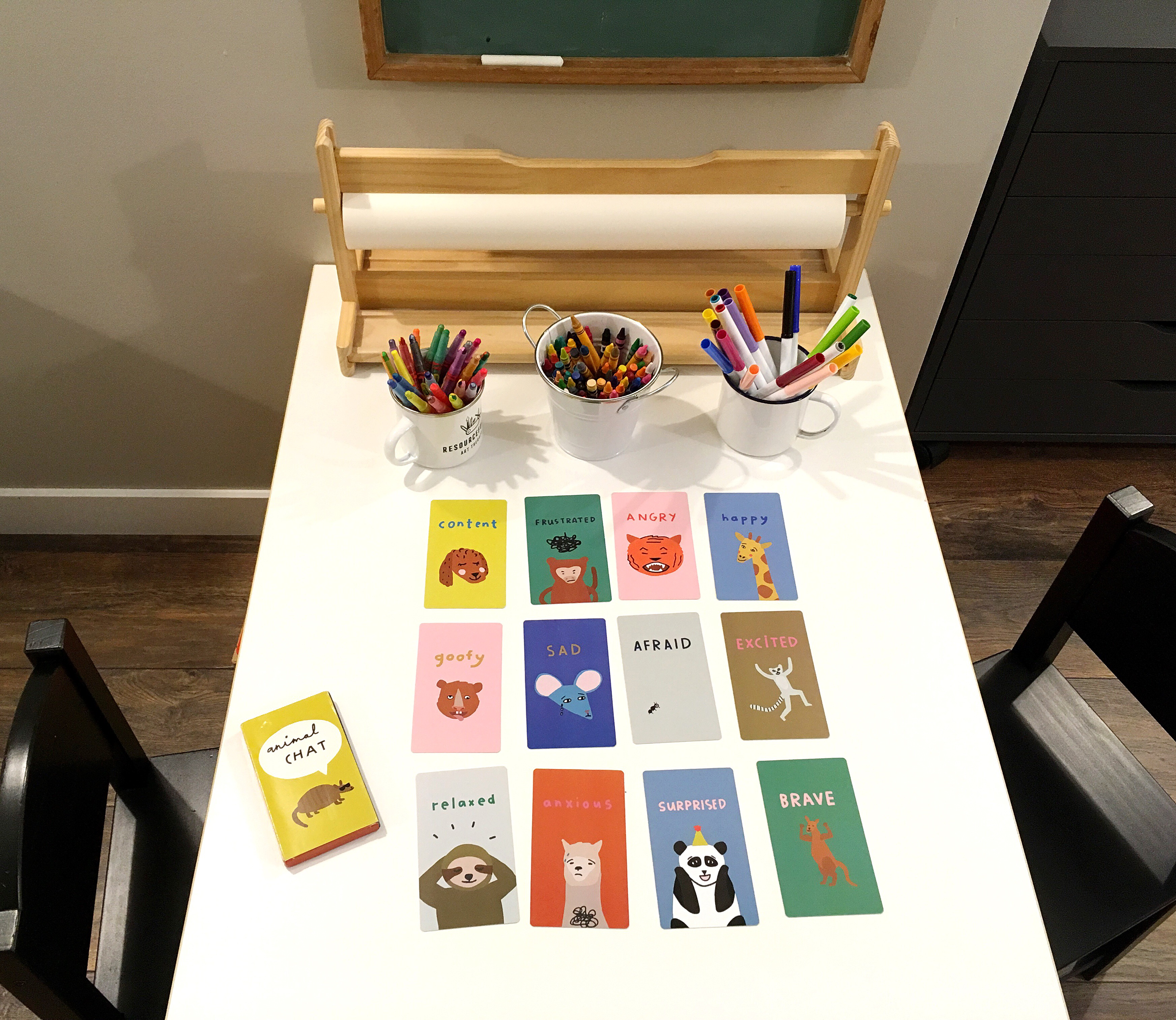"""Art supplies and """"Animal Chat"""" feelings cards arranged on children's table"""