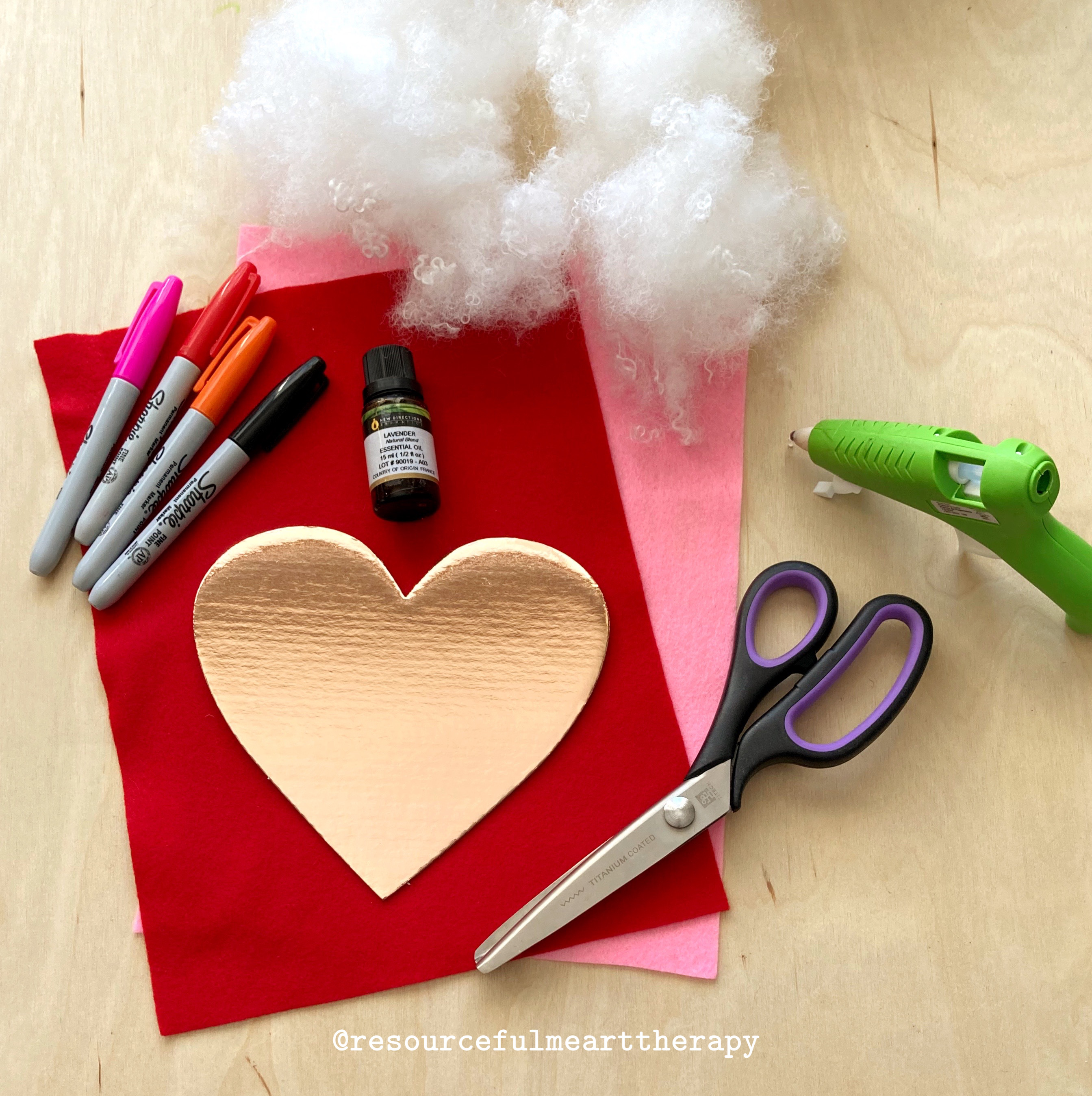 Photo of felt, cardboard heart, scissors, stuffing, hot glue gun, sharpies, and lavender essential oil.