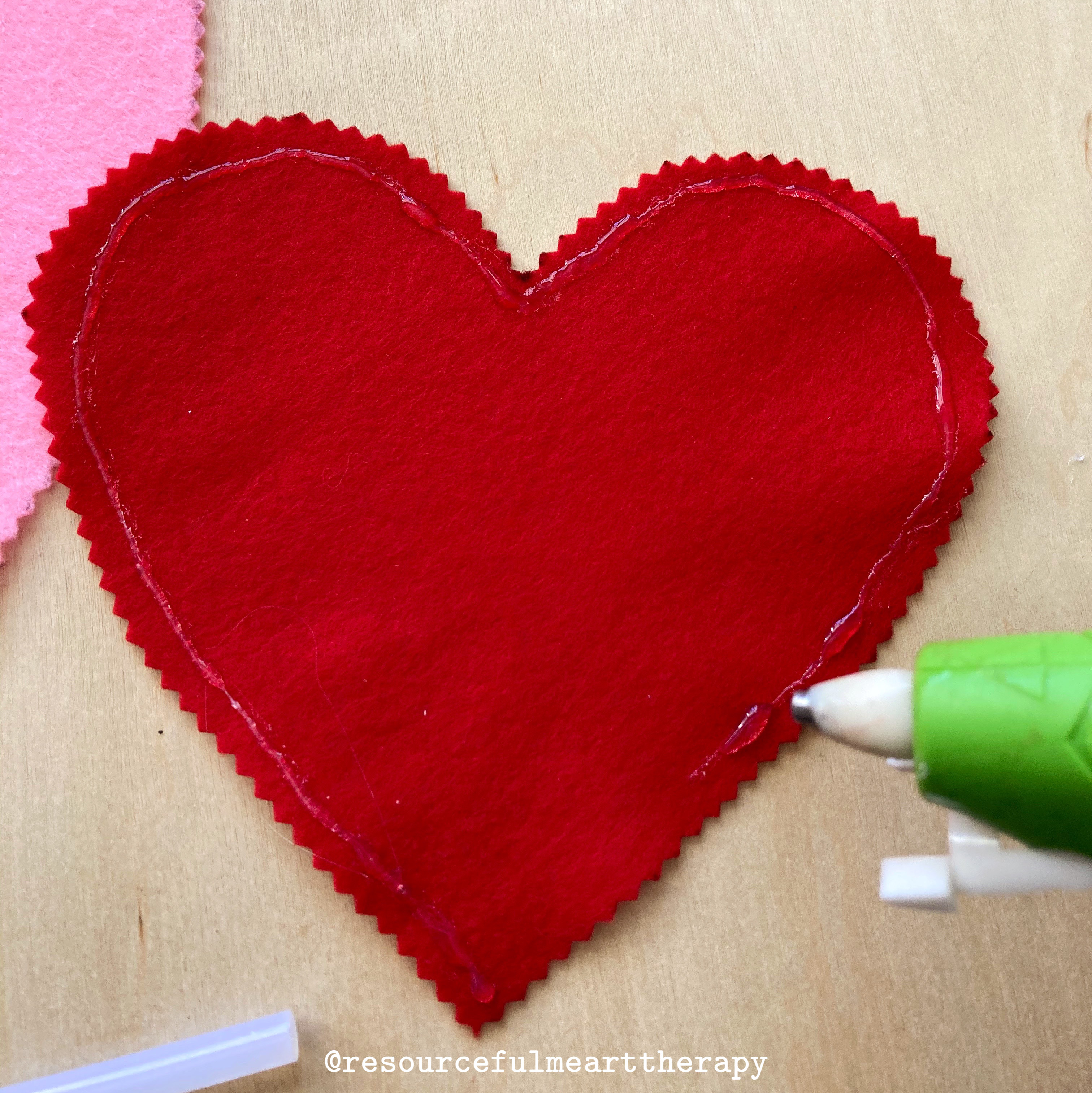 Photo of hot glue along the edge of a cut out felt heart shape, with a small space without glue