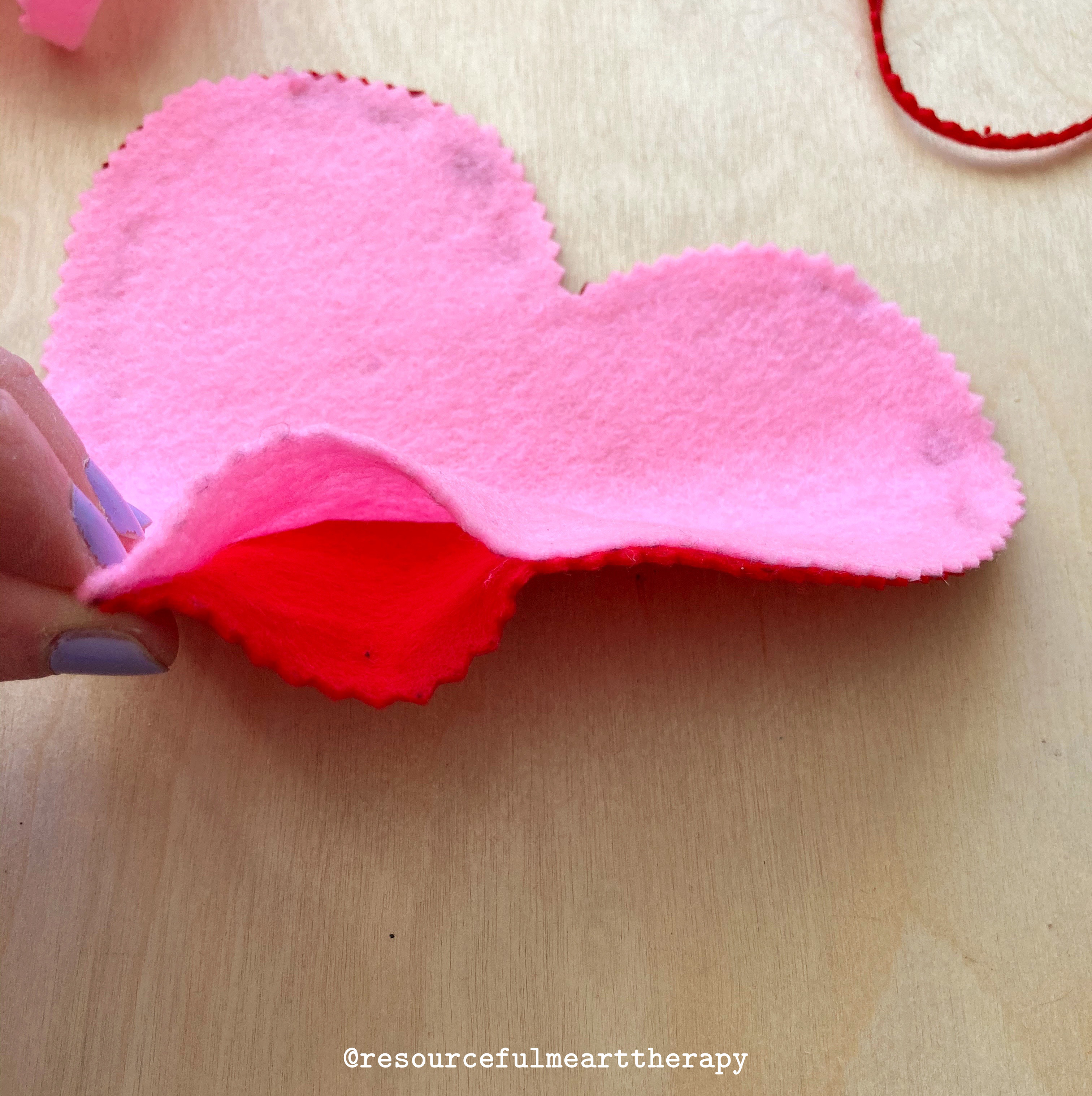 "Photo of two felt heart shapes glued together, with a small ""opening"" left to add stuffing"