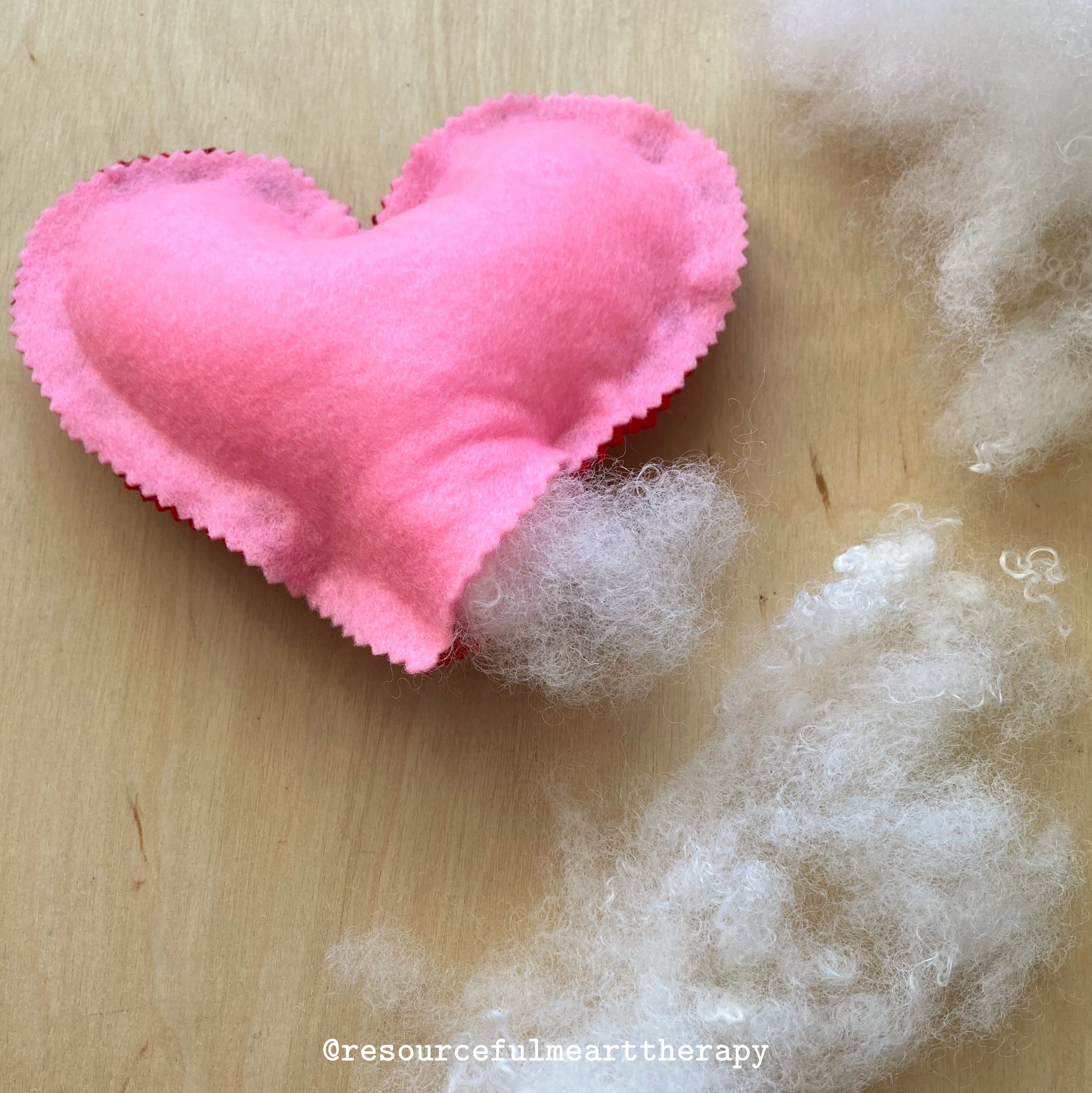 Photo of small heart pillow being stuffed with stuffing