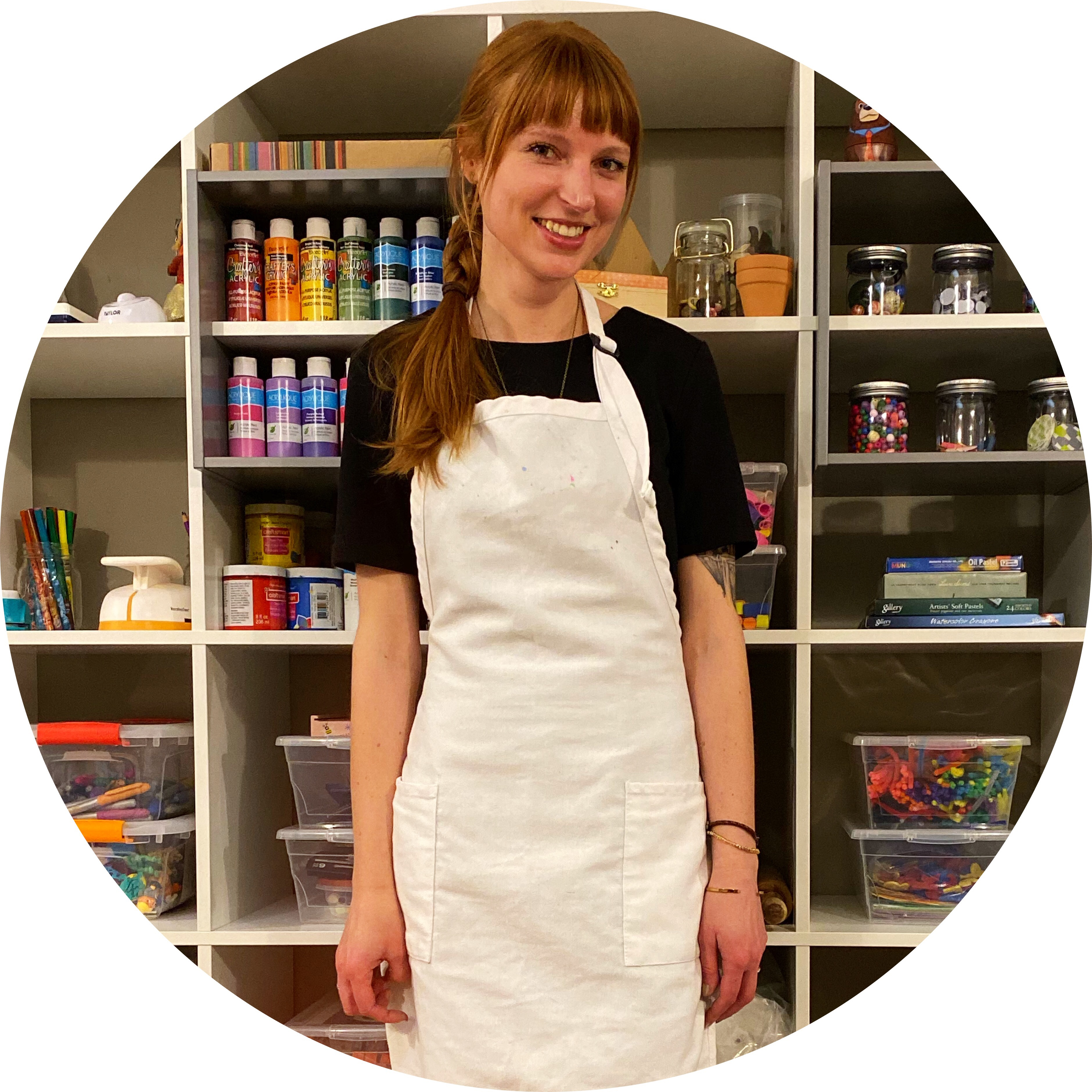 Woman wearing apron standing in front of a shelf of art supplies