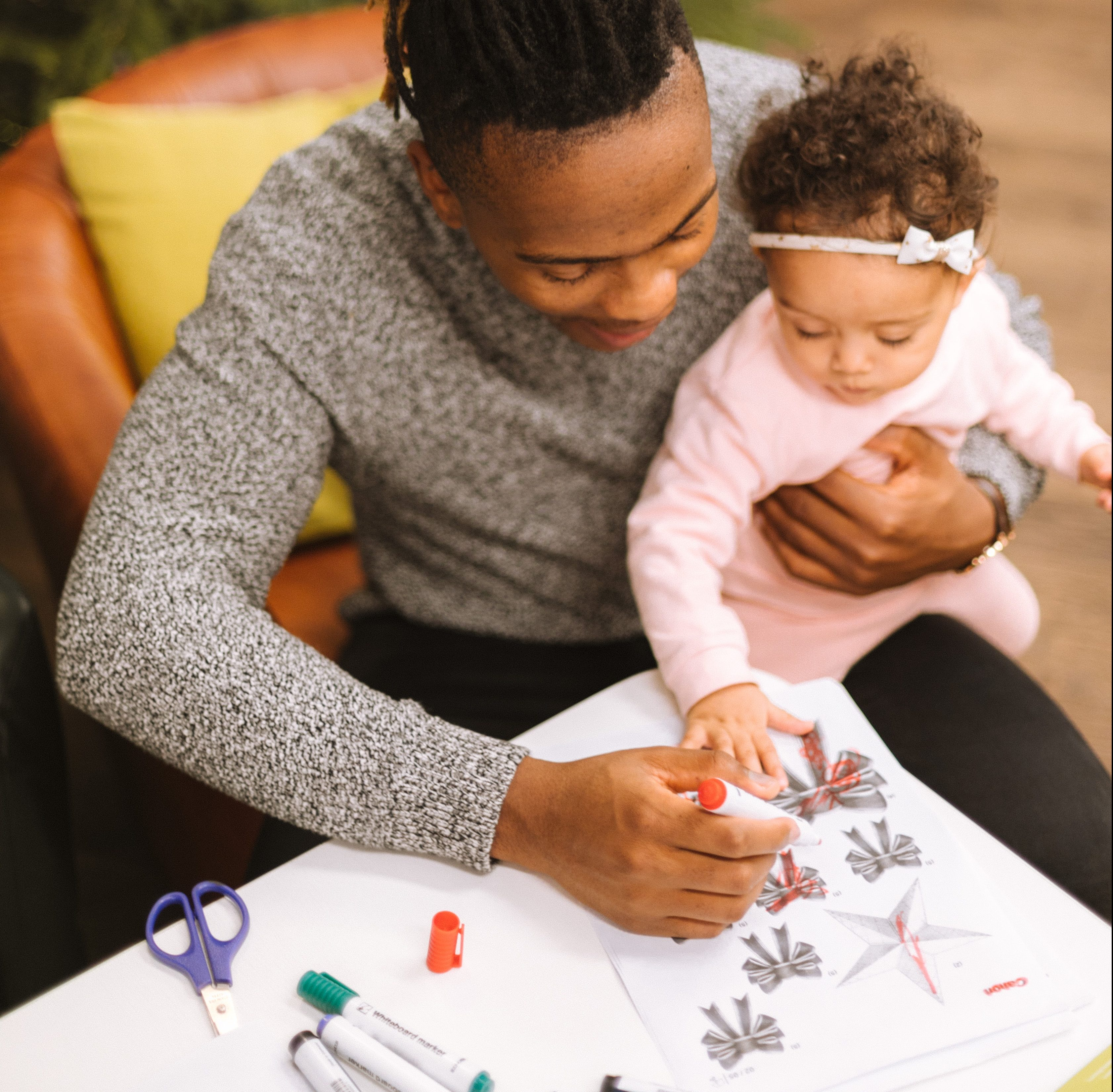 black man holding small child and drawing together with markers