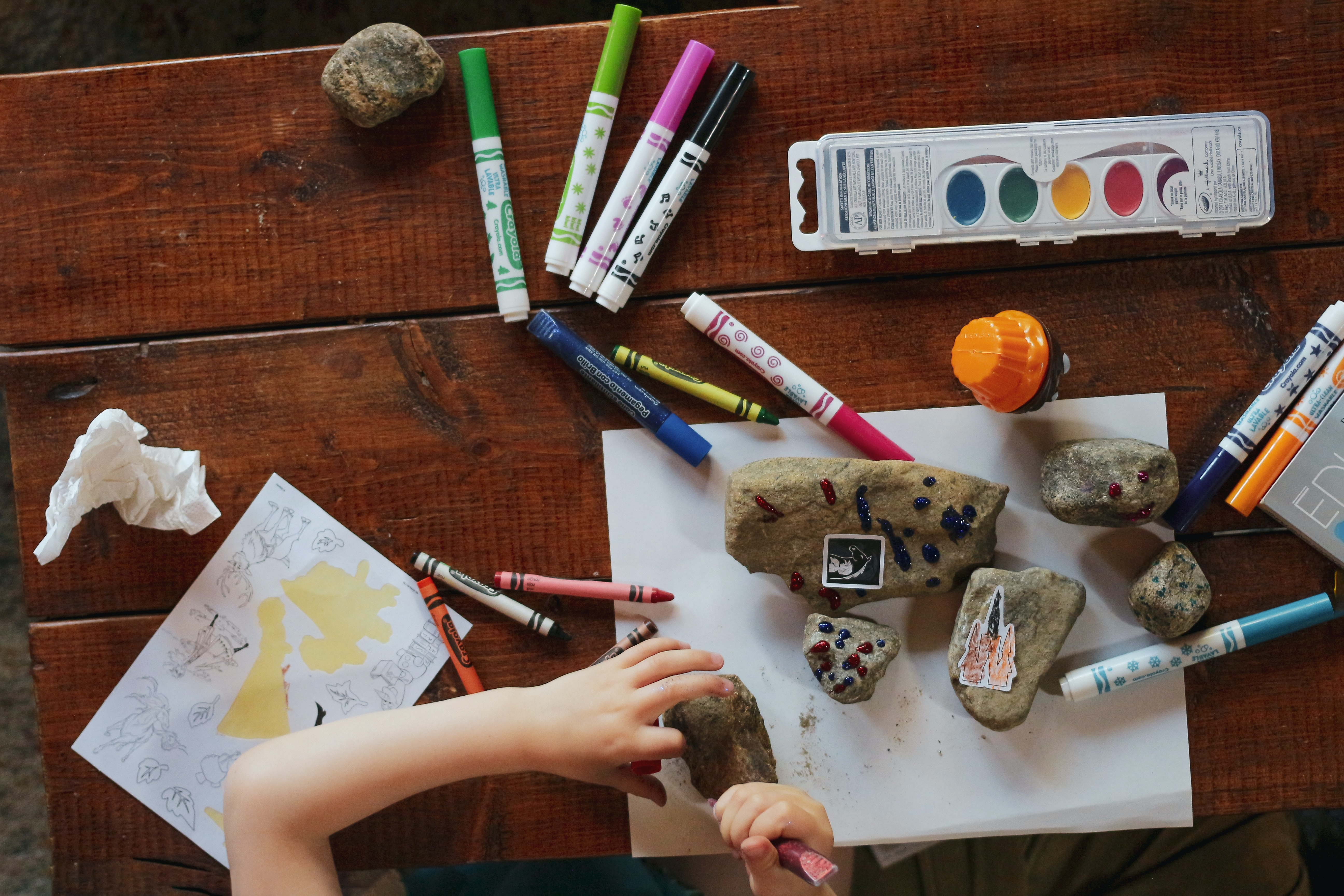 child decorating rocks with stickers and glitter glue
