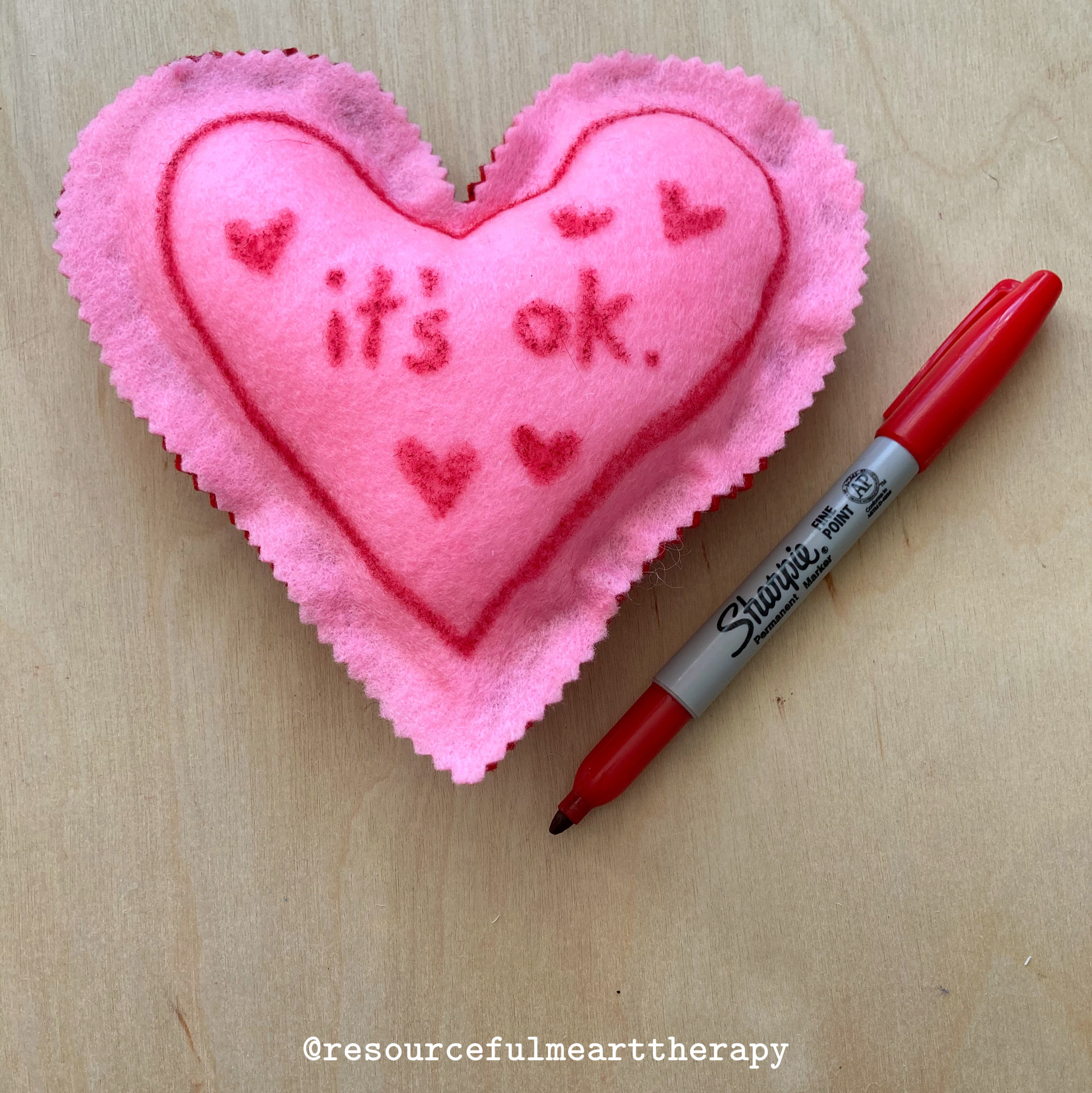 "Heart shaped felt pillow decorated to say ""it's ok,"" with red hearts. Red sharpie marker beside pillow."