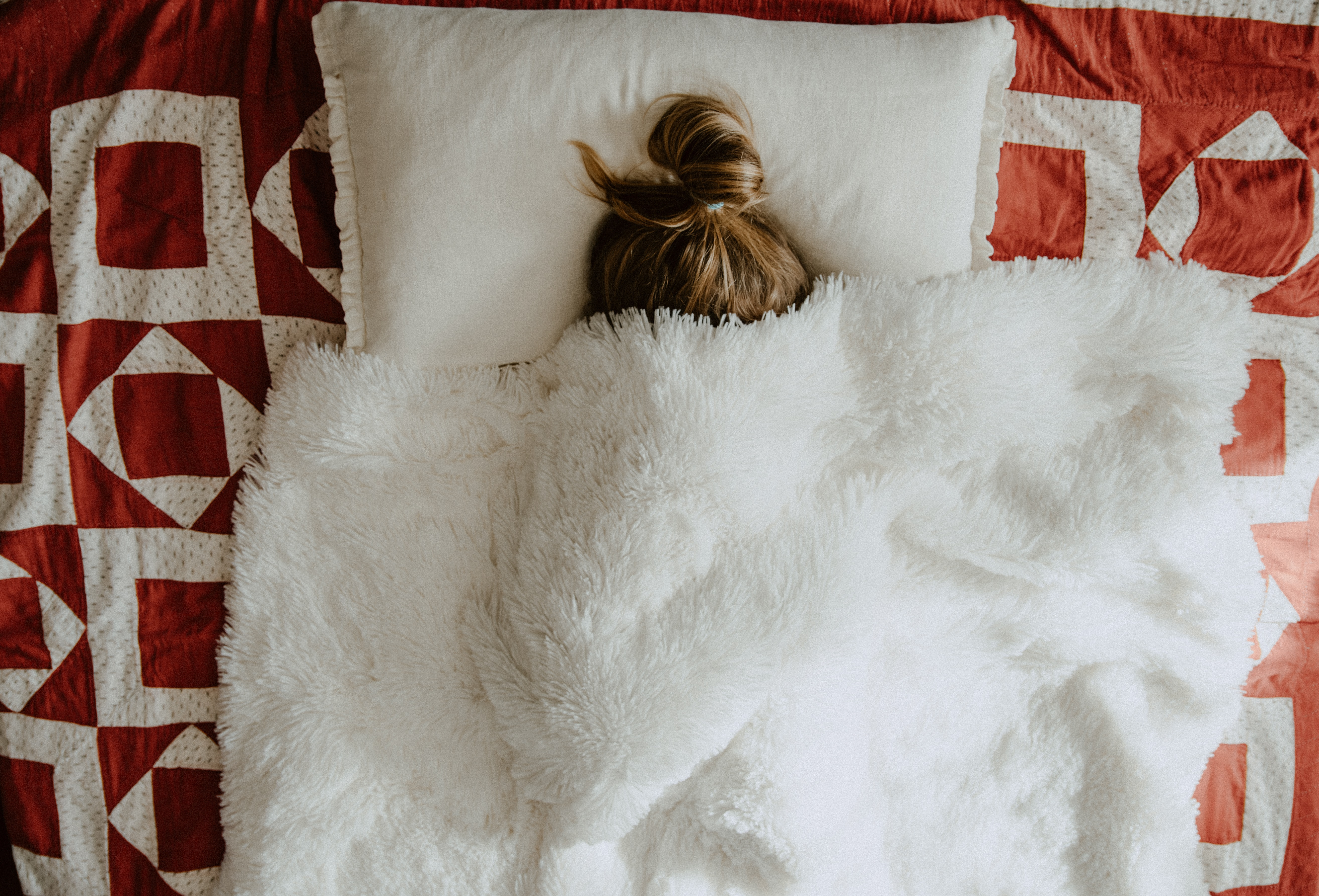 child hiding under blankets in bed, only messy bun is visible
