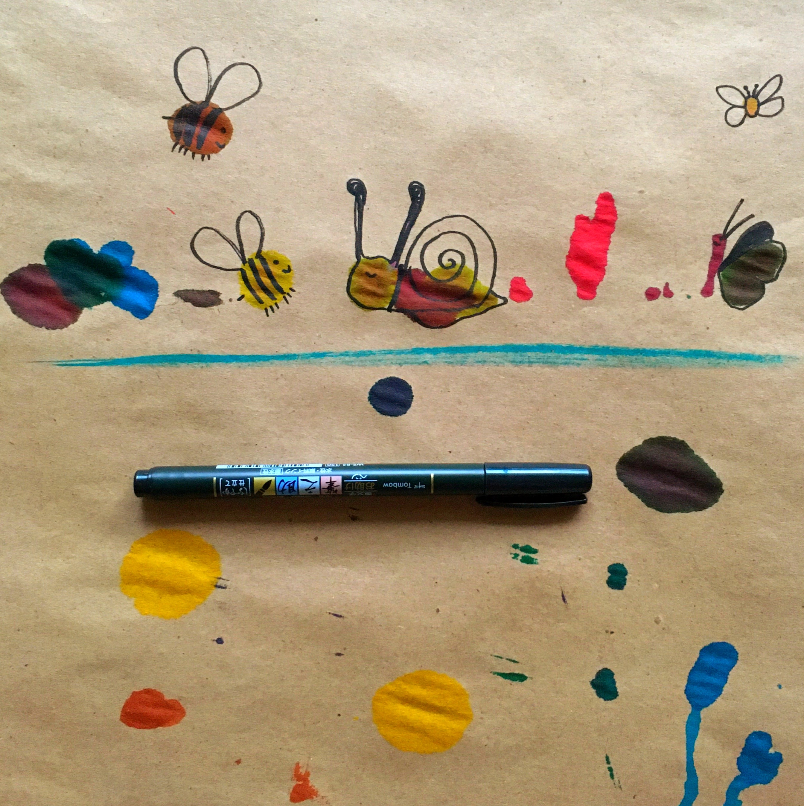 doodles of bugs made from paint splatters on craft paper