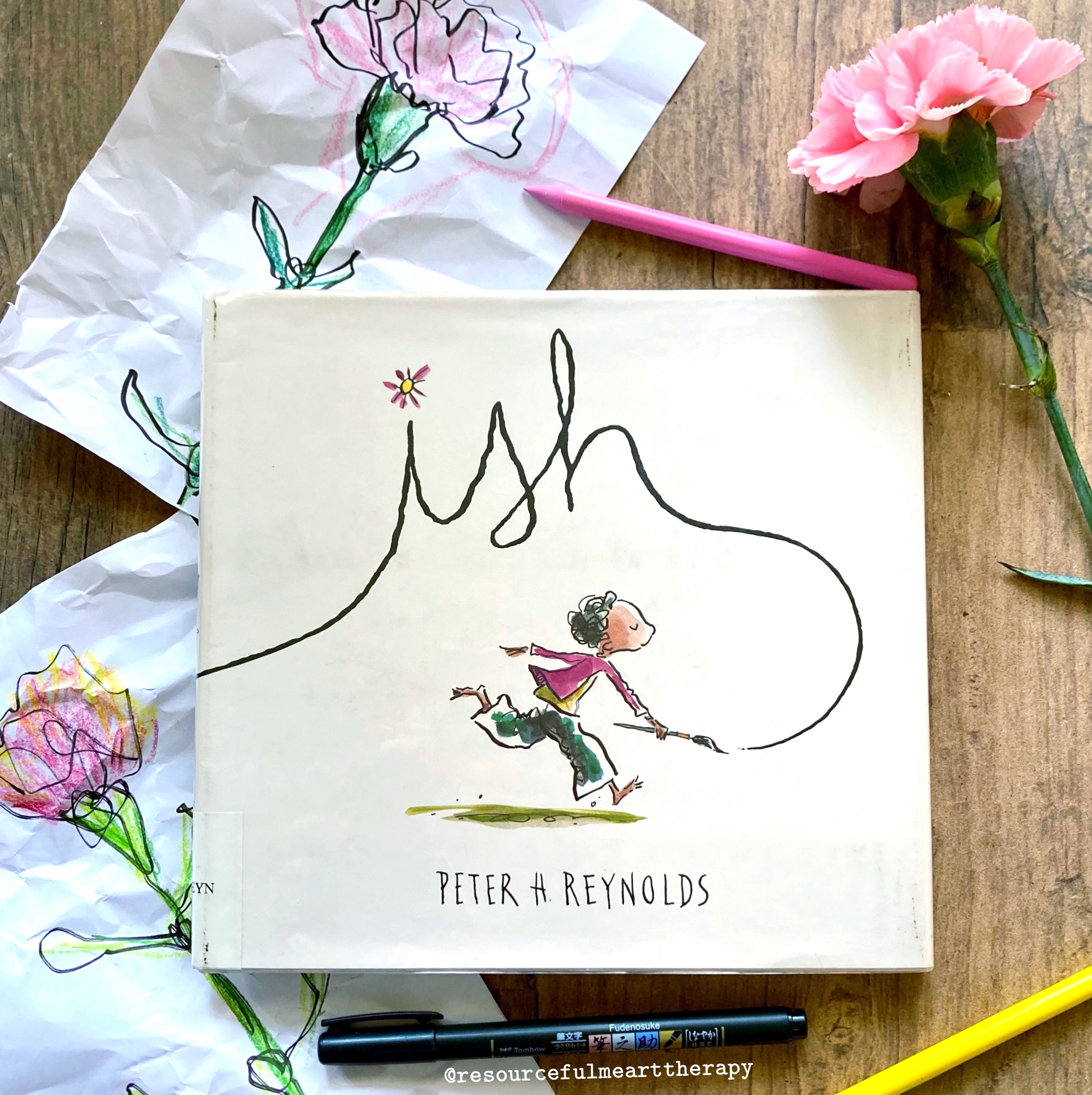 """Photo of the children's book """"Ish"""" by Peter Reynolds, surrounded by crumpled drawings and a pink carnation"""