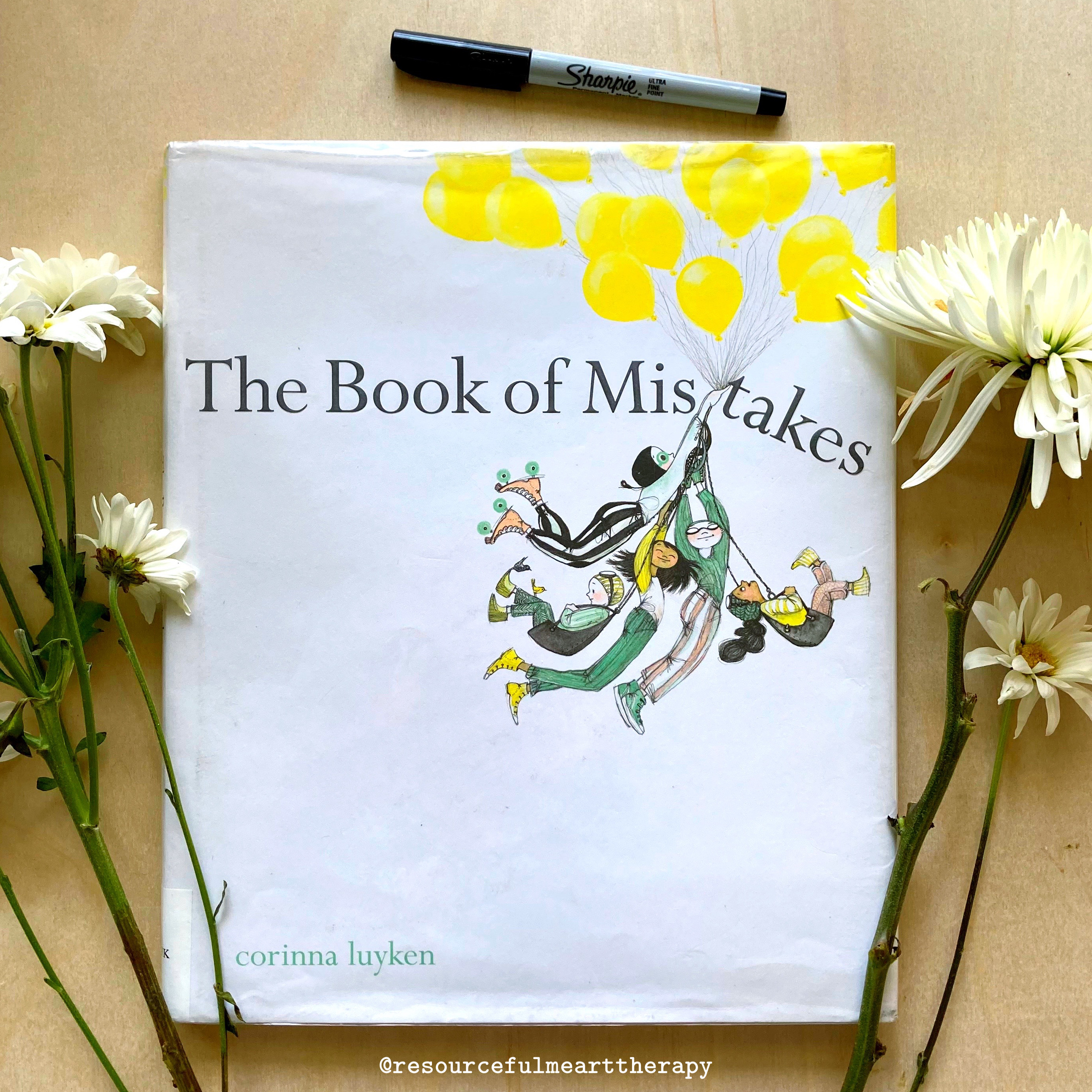 """Photo of the children's book """"The Book of Mistakes"""" by Corinna Luyken, surrounded by cut flowers"""