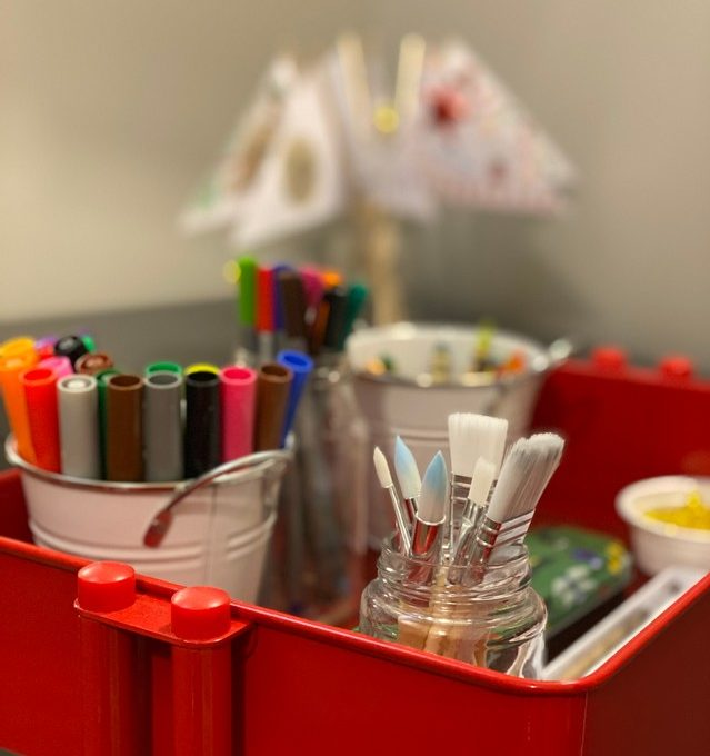 Close up photo of art supplies on red storage cart