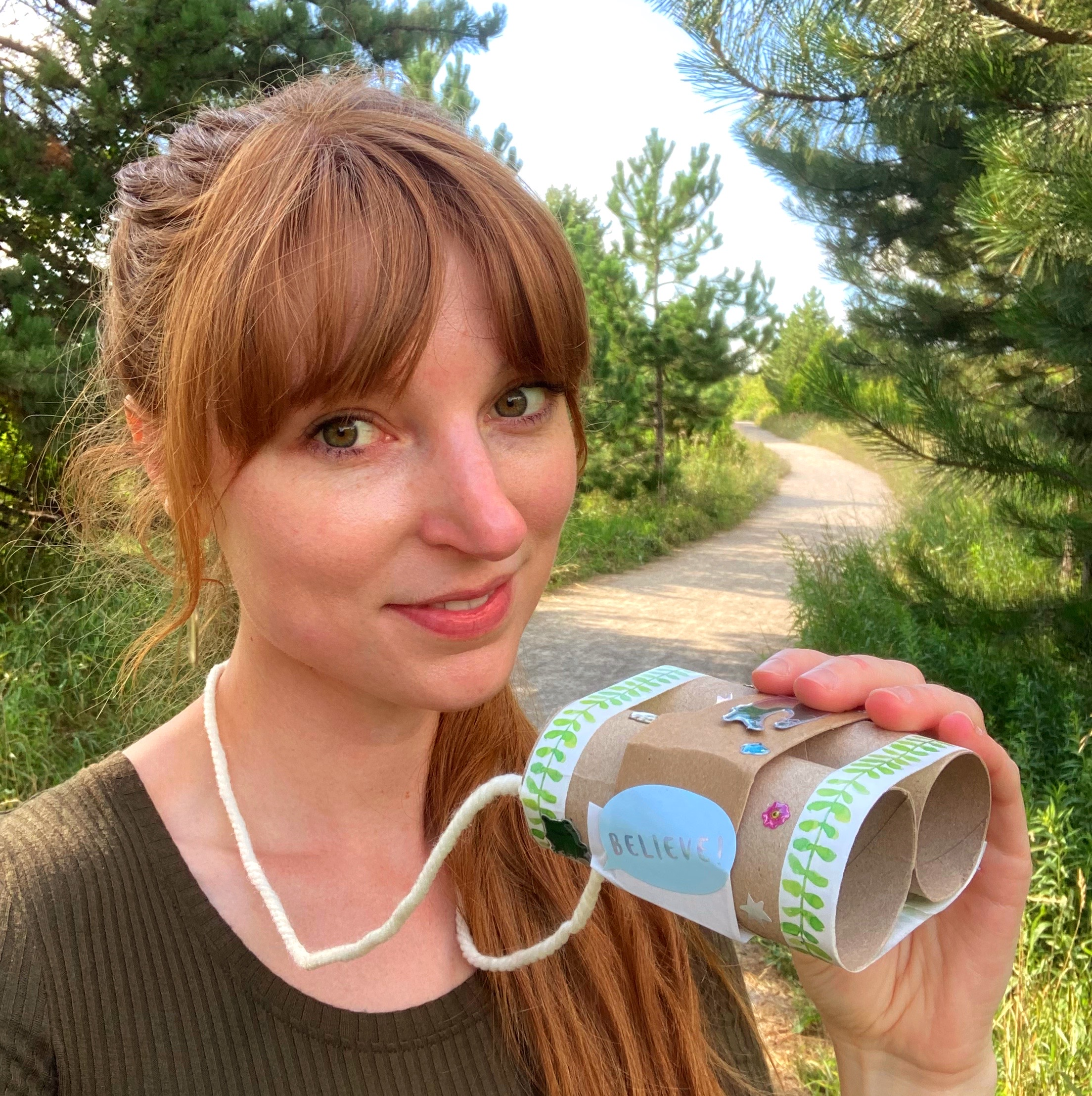 Photo of Rubi holding the toilet paper roll 'binoculars' she made and standing on a path in the forest