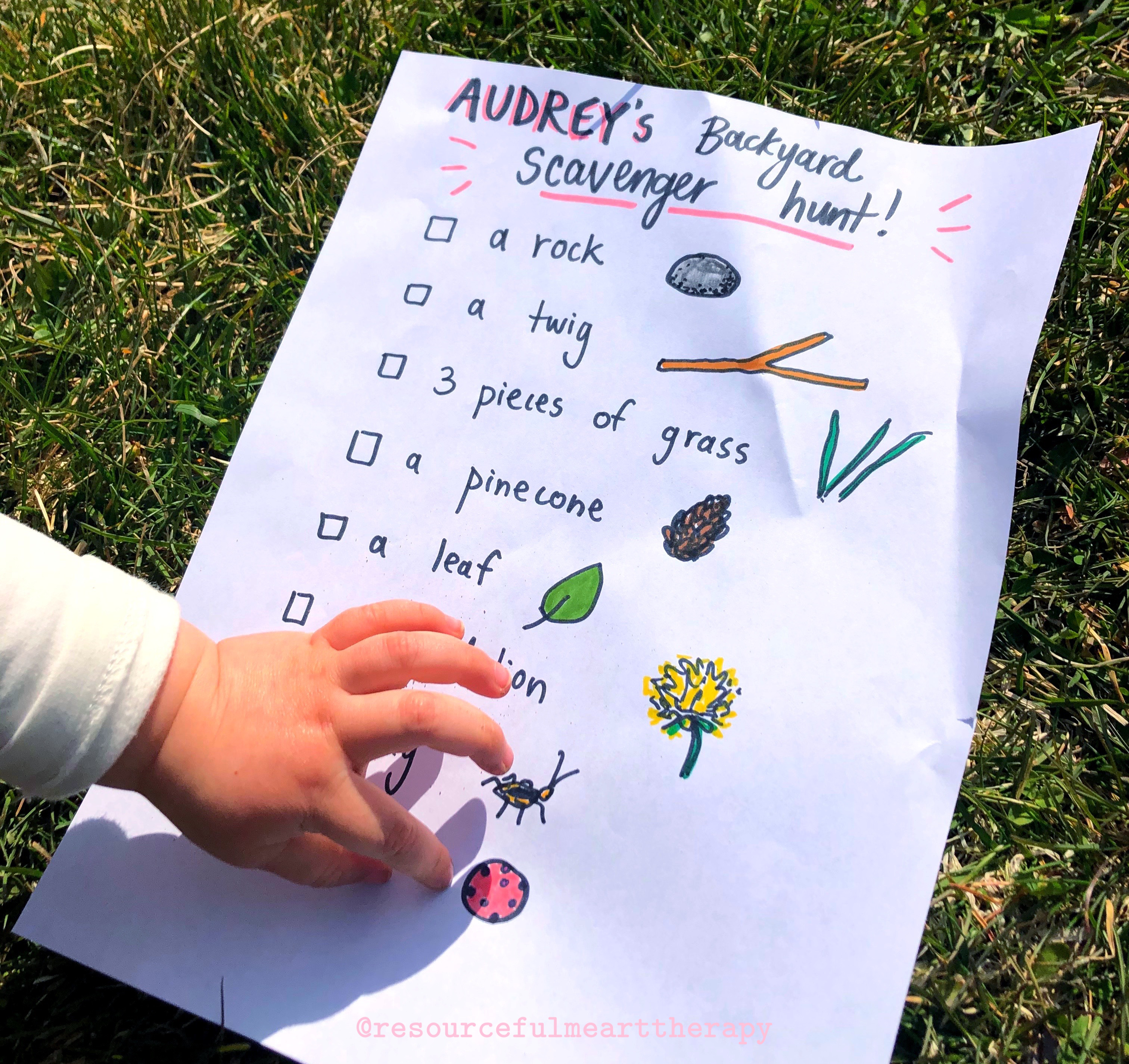 """photo of a child's hand pointing to an item on """"Audrey's Backyard Scavenger Hunt"""" - a list of nature items that can be found in the backyard written on a piece of printer paper. There is a simple illustration beside each item."""