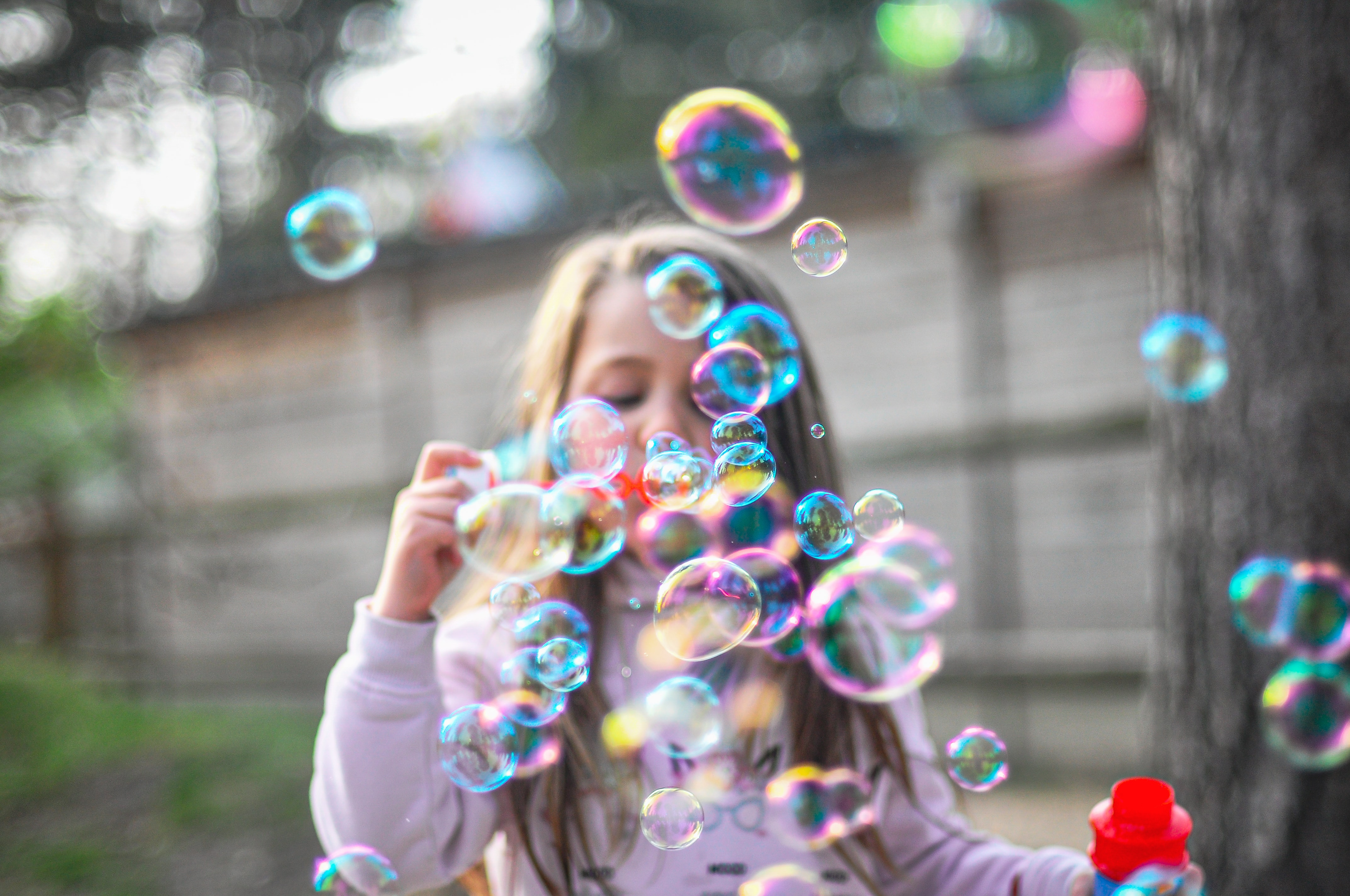 Child standing outside blowing bubbles