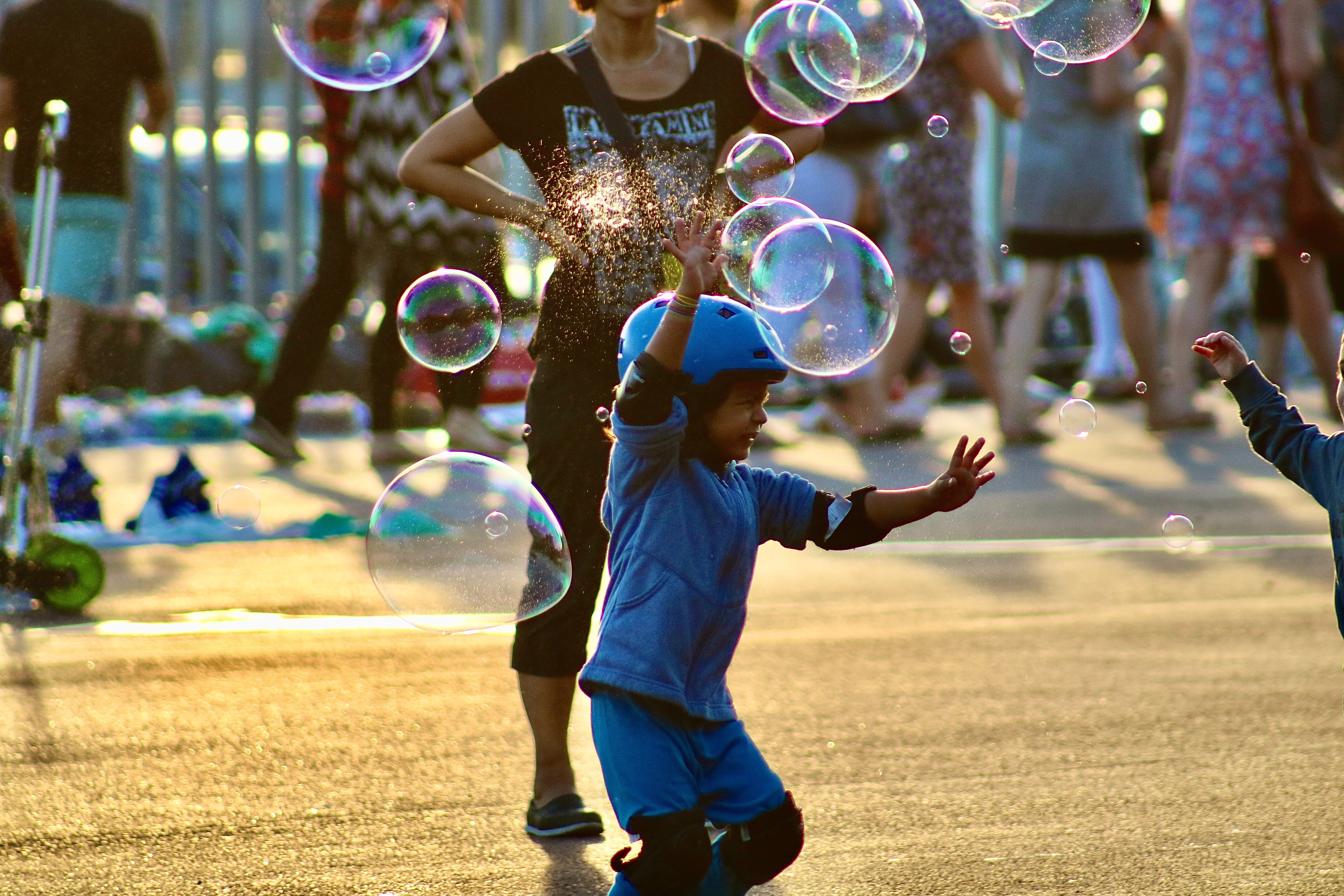 Child wearing helmet and knee pads jumping to catch bubbles in the air